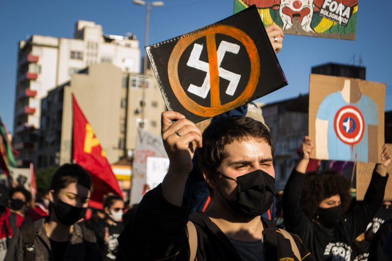 На передньому плані протестуючий у чорній масці тримає знак із перекресленою свастикою.